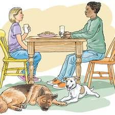 An Afro-American woman talks to a young girl across a table, two dogs are asleep on the floor