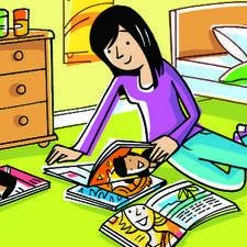 Teenage girl reading magazines in her bedroom.